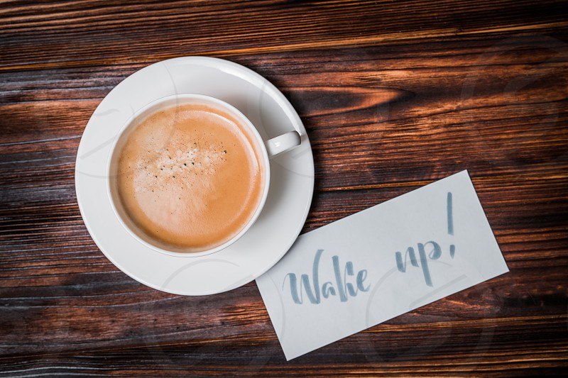 Wake up text near cup of coffee. Font of lettering word on white paper by calligrapher. Morning handwriting lettering concept. photo
