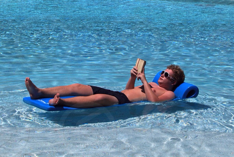 Relaxation pool reading sunshine hot laid back cl loll photo