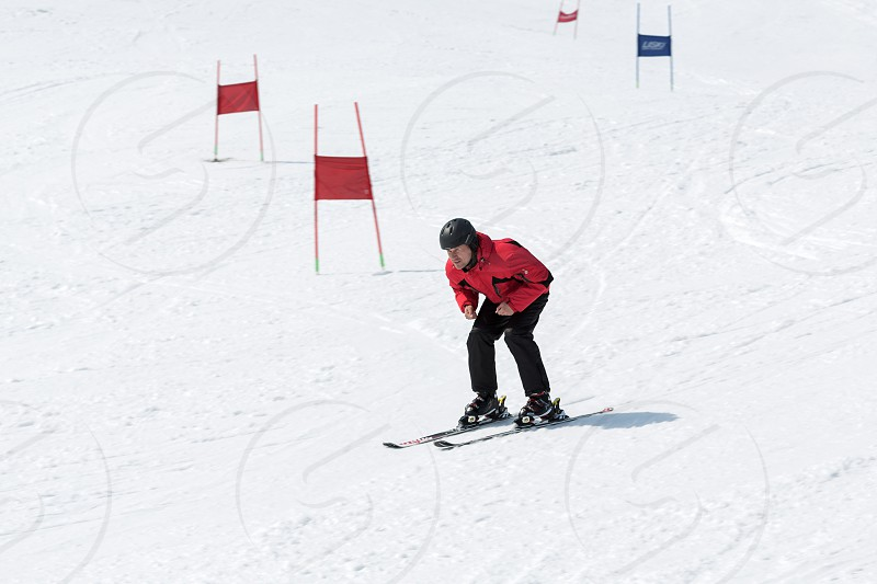 MOROZNAYA MOUNTAIN YELIZOVO KAMCHATKA RUSSIA - APR 17 2015: Skier in red and black outfit coming down the slope without ski sticks on sunny day. Russian Federation Far East. Kamchatka Peninsula. photo