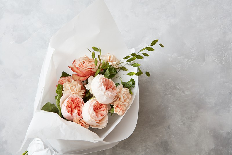 Beautiful pink roses of bouquet with white paper on a gray stone background flat lay photo