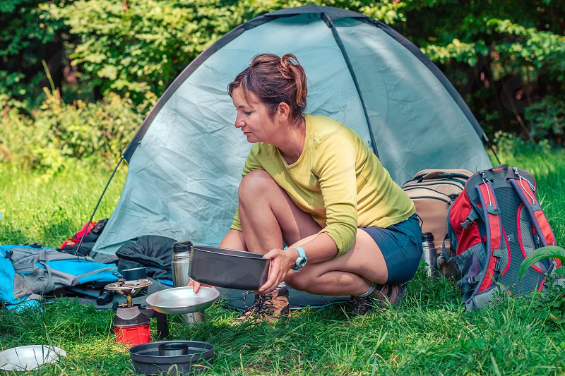 Spending a vacation on camping. Woman preparing a meal outdoor next to tent photo