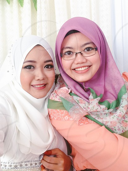 two woman wearing hijab head scarves photo