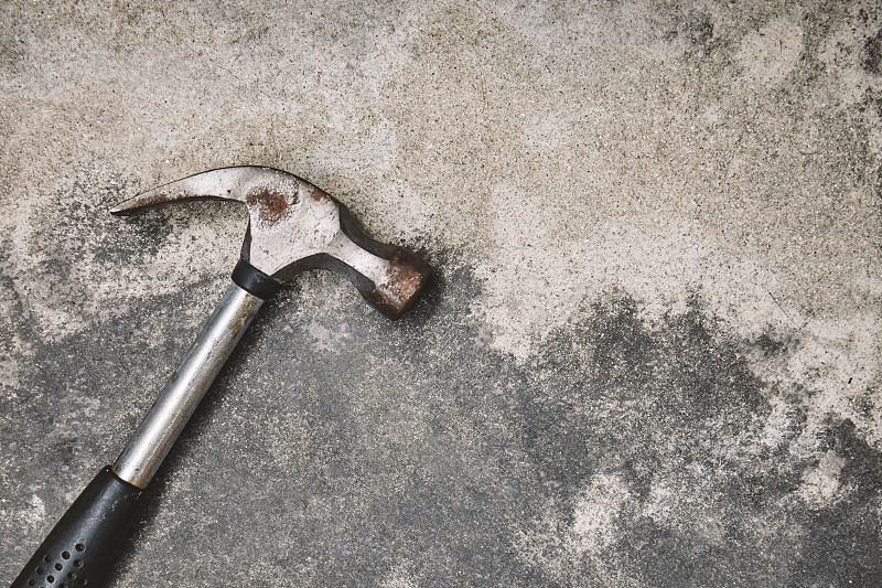 Home working tools for repairing Old steel hammer with oxide on dusty cement background with copy space photo