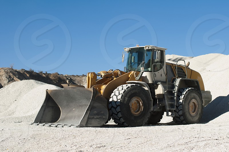 Excavator in a limestone quarry.Piles of limestone rocks photo