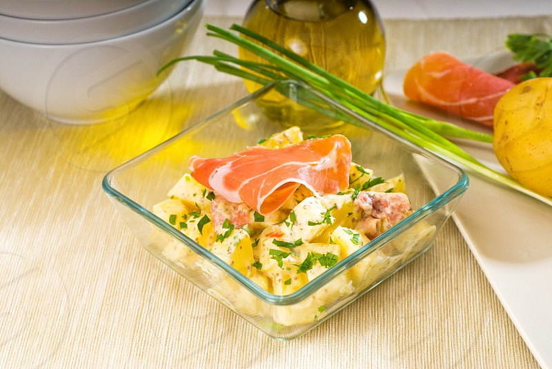 fresh home made parma ham and potato saladwith raw ingredients around with bowls and dishware on a table photo