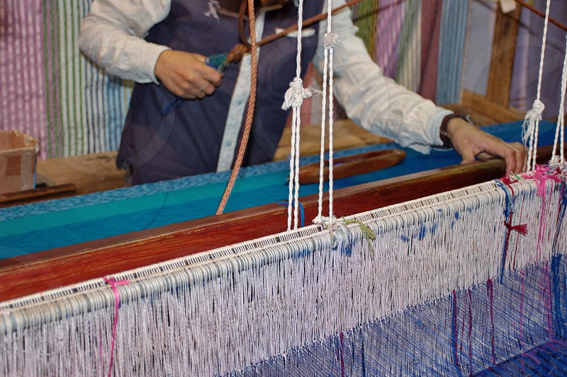 Midsection of a man at weaving loom photo