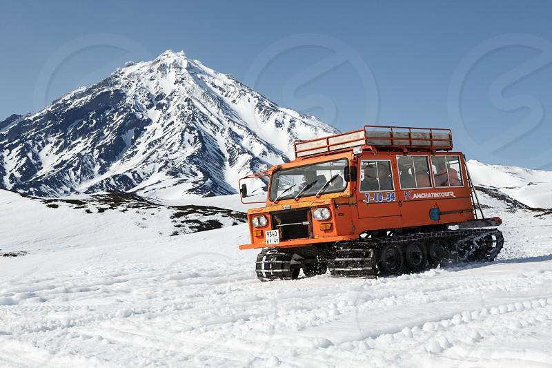 KORYAKSKY VOLCANO KAMCHATKA PENINSULA RUSSIA - APR 26 2014: Snowcat transportation sportsman (skiers and snowboarders) on snowy slopes of mountains on background of beautiful stratovolcano. photo