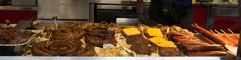Various meats on a griddle -- sausage spirals sausage links onions cheeseburgers and hamburgers corn dogs fair or festival photo