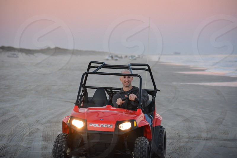 man fun driving orange red ATV beach sand water natural light photo