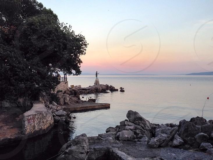 Sea statue rocks sunset photo