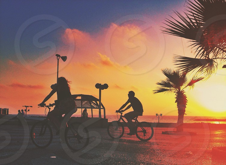 2 person riding on bike on sunset view photo