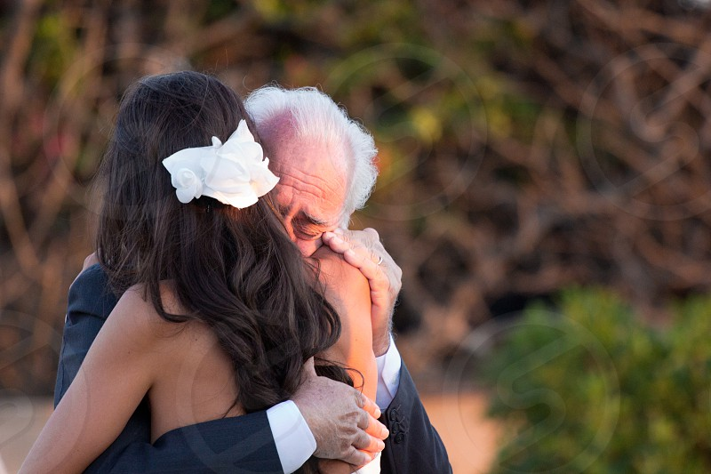 man being emotional hugging the woman in white floral hair pin photo