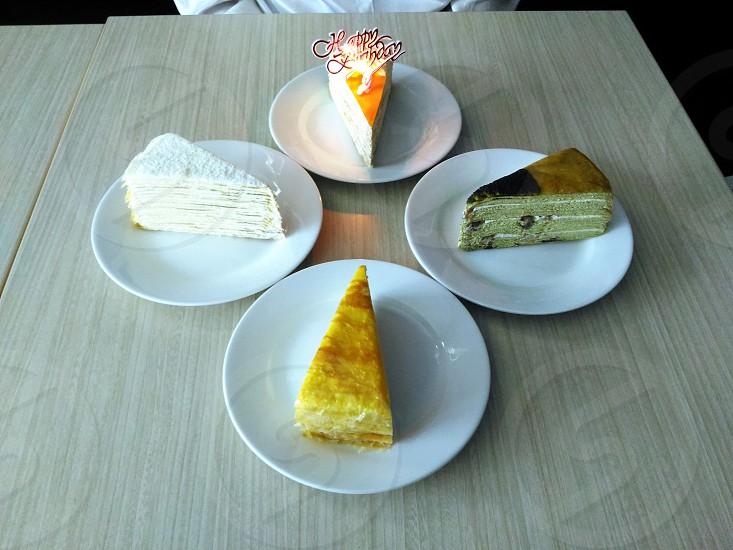 white cream pancake and chocolate cake on 4 round ceramic plate photo