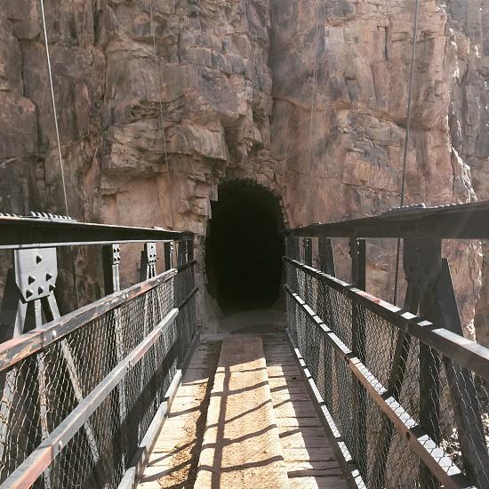 brown concrete bridge near cave during daytime photo