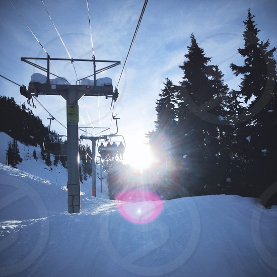 Riding Ski Lift into sun Whistler BC photo