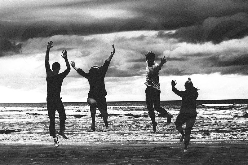 group of people jumping on beach photo