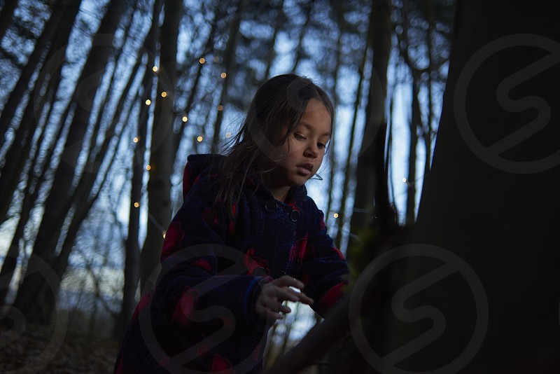 Young Asian girl in a forest at dusk in autumn surrounded by trees and string of lights scattered around photo