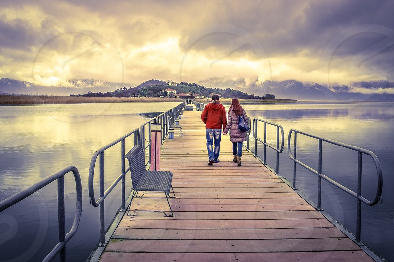 Young Couple In Love Walking Across A Bridge Holding Hands - Greece photo