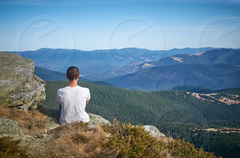 sky green outdoors one view rock high peak travel person nature freedom terrain journey activity solitude landscape adult summer relaxation leisure day mountain looking beauty environment forest top extreme human tourist horizontal horizon cliff remote recreational distant viewpoint backpacker  photo