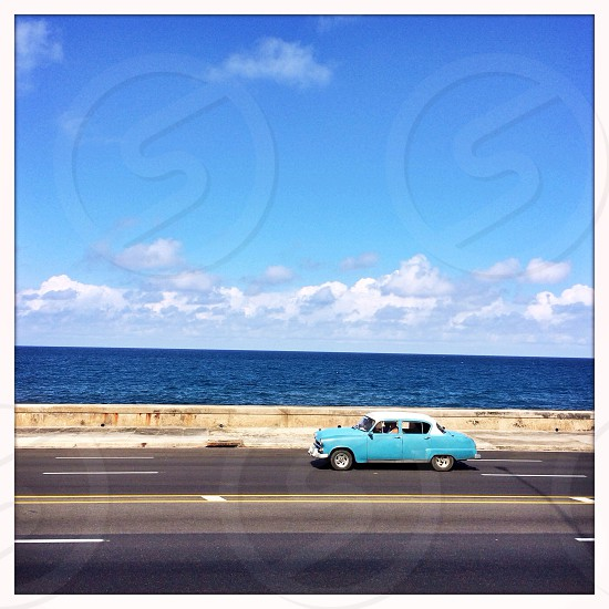 A classic car drives along the Malecon in Havana Cuba. photo