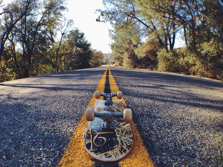 view of upside down black skateboard on gray road with yellow lines photo