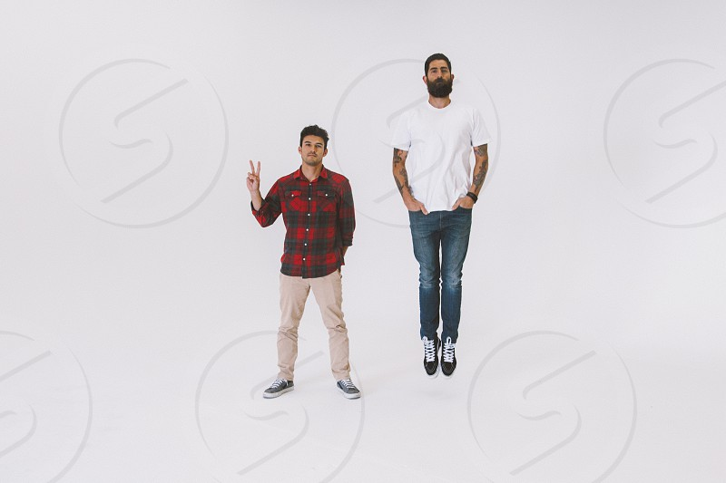 man jumping and man holding peace sign photo