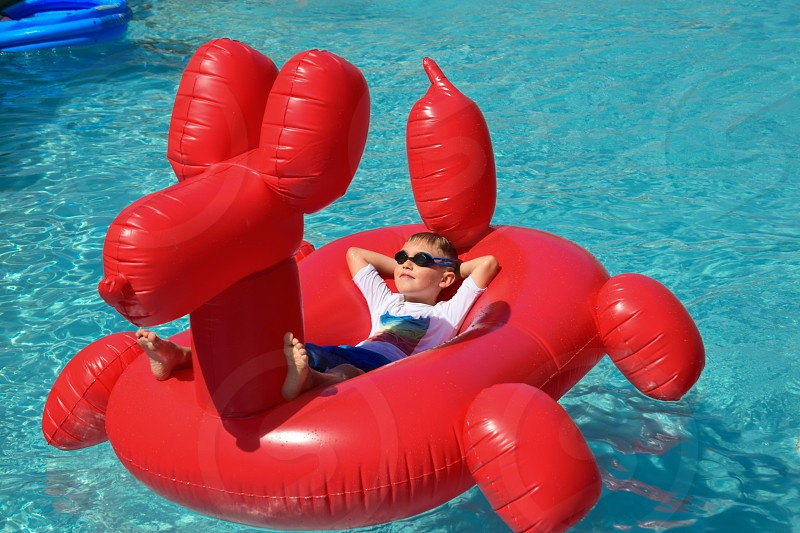 Young boy lounging on a big float in a swimming pool photo