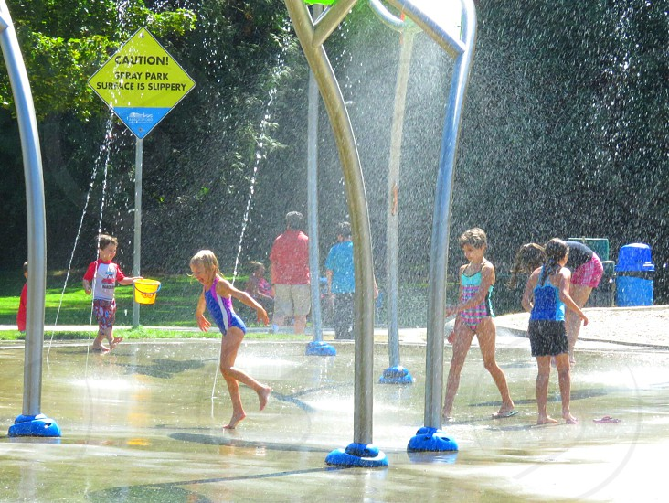 Children play on a sunny day in an outdoor water park for physical summer fun. photo