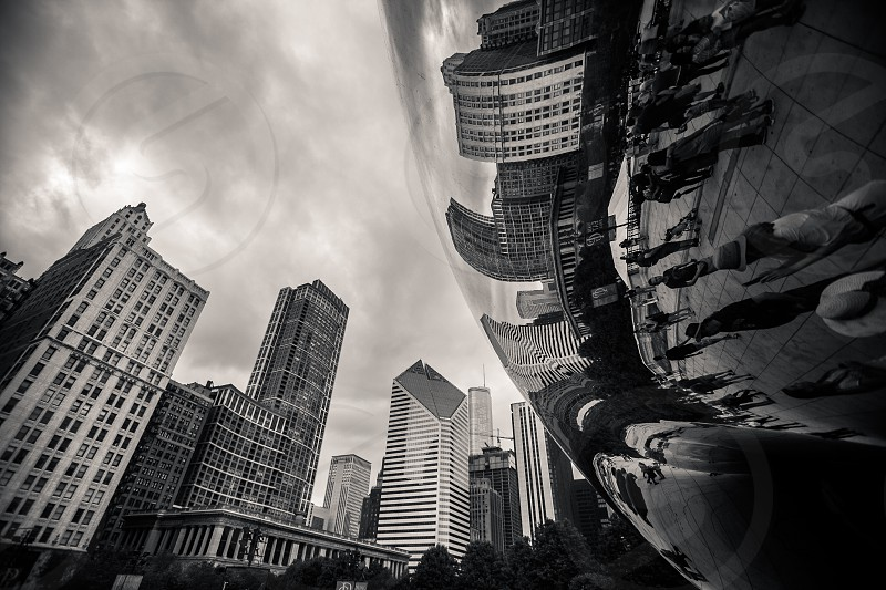 The city of Chicago and its dark skies reflecting against the 'Bean' Cloud Gate in Millennium Park. photo