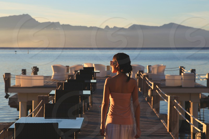 woman in beige tube top standing on brown wooden dock photo