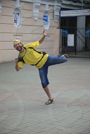 man doing arabesque position wearing yellow cap yellow and black shirt and blue denim shorts holding black dslr camera during daytime photo