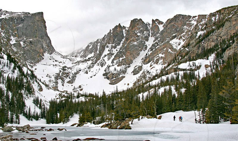 Snowshoers at frozen Dream Lake in Rocky Mountain National Park during winter photo