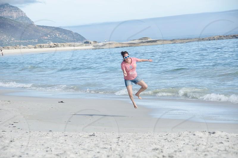 Woman havingfun on beach jumping for joy! photo