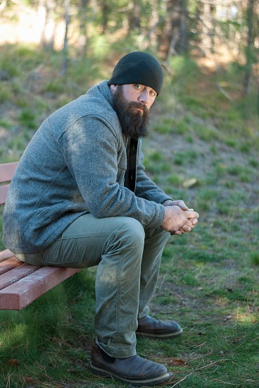 Bearded man sitting on bench in the outdoors looking at camera photo