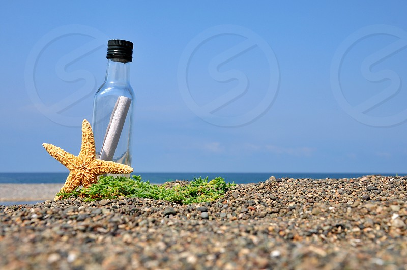 white rolled paper inside clear glass bottle beside starfish on sea pebbles photo