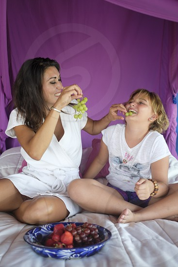 Mother and daughter having fun at eating grapes from a fruit bowl in bed photo