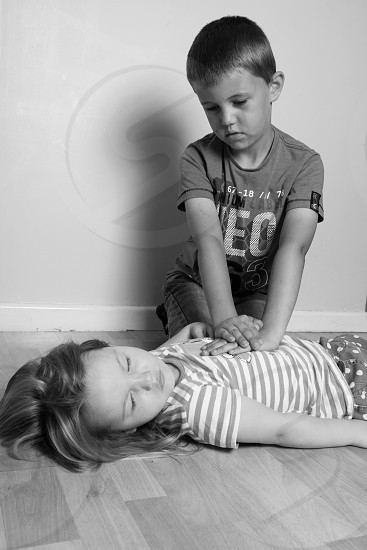 little boy practicing cpr on little girl photo