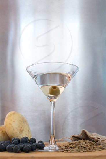 martini with green olive on table with grapes and potatoes photo