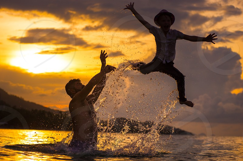 Silhouette of two people: father and his hipster son at the beach. Boy in wet clothes fluttering above the water surface while daddy pushes him out of the water photo