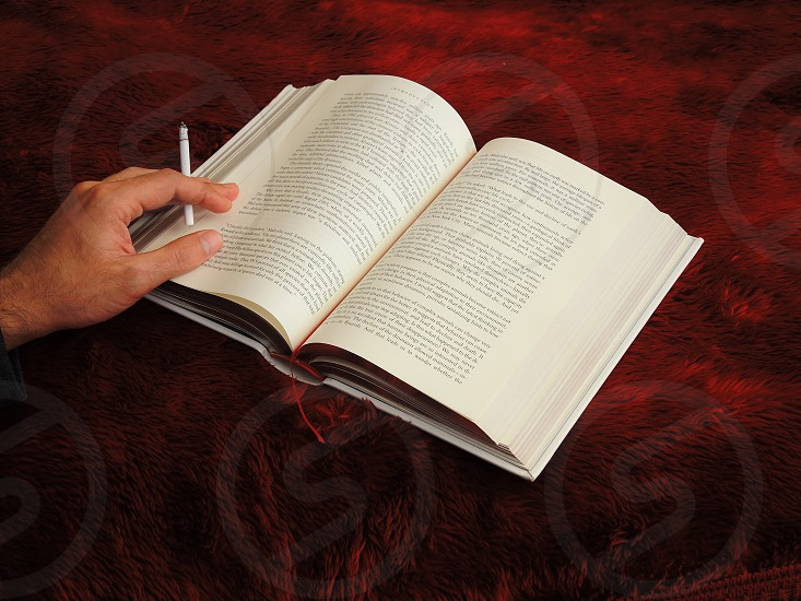 white cigarette stick on left hand near book photo