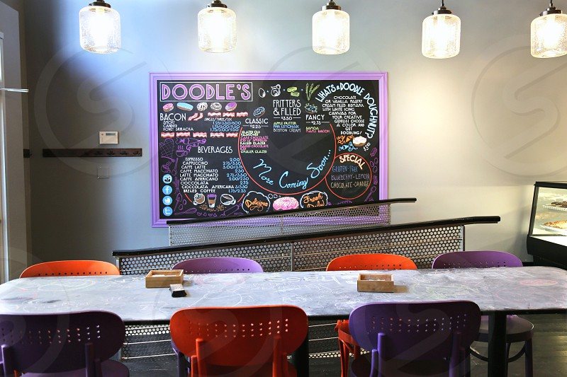 7 orange and purple chairs beside gray rectangular table near purple framed black chalkboard photo