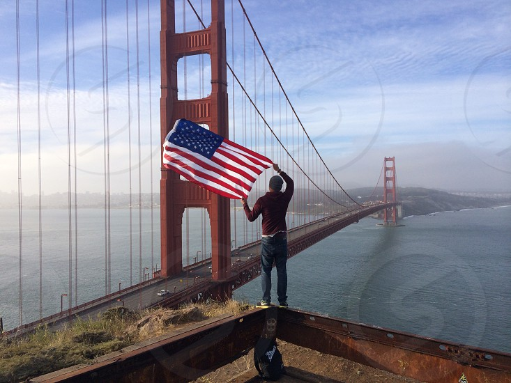 golden gate bridge and person with flag photo