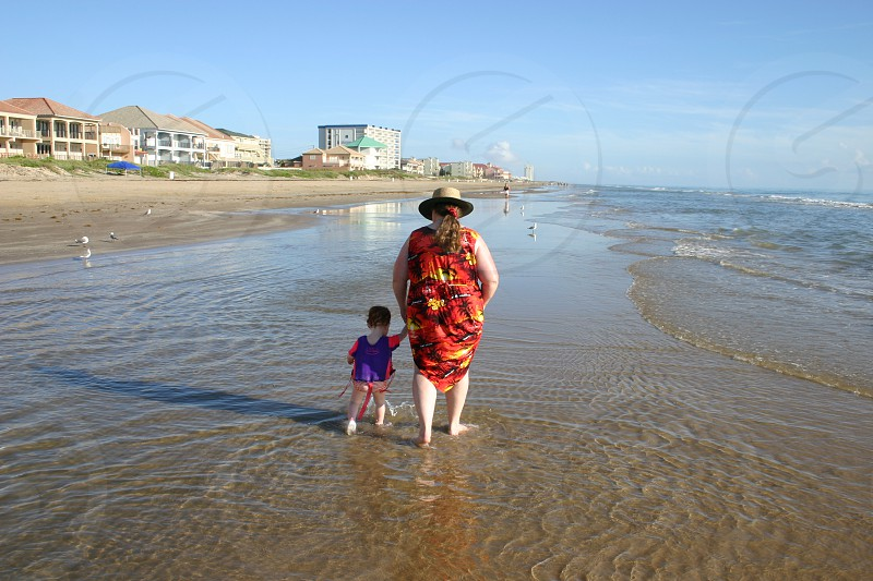 Woman and toddle strolling hand in hand through the surf of a beach on a sunny day. photo