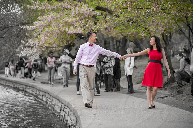 Asian couple holding hands stroll walk love engagement red dress bow tie cherry blossums lake romance photo