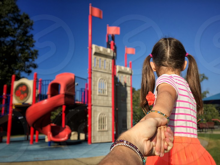 Come follow play with me playground outside clear day blue Sky green tree red slide castle flags hold hands mom daughter fun together bond pigtails summer photo