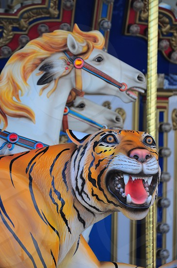 tiger figure beside yellow and white horse figure photo