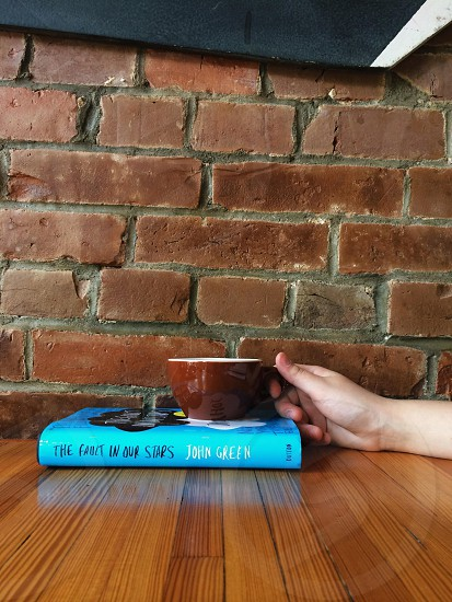 white and brown ceramic mug on blue book and brown wooden surface photo