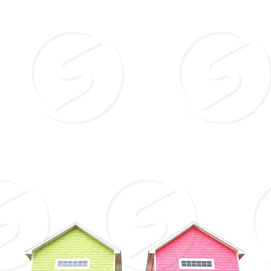 view of green concrete house beside pink concrete house photo