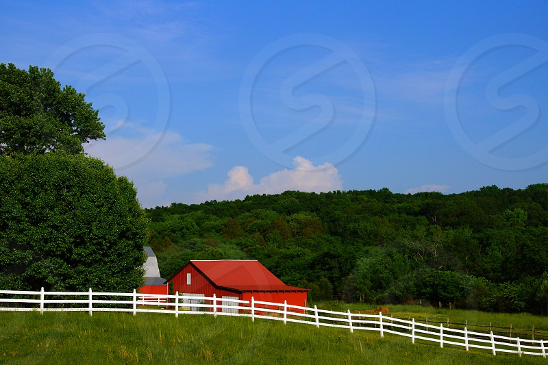 red wooden barn in the middle of farm photo