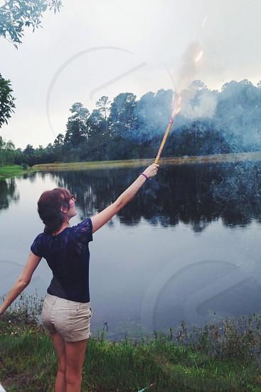 woman in blue shirt lighting a firework photo